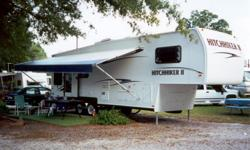 2001 Hitchhiker II 5th Wheel Travel Trailer with many extras. Rear bay windows. 13' living room slide out. Free standing solid oak table with four chairs. Solid oak cabinetry. XL queen bed. Shower with large dressing area & closet. Couch with double hide