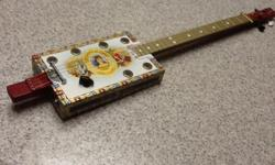 La Aroma De Cuba brand new hand made 4 string fretted acoustic/electric Cigar Box Guitar. This guitar has a beautiful sound for a cigar box guitar. It's one of my best ones. It has a piezo transducer in the hot spot in the box covered with silicone to