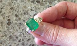 "One Emerald cut emerald in the center with five baguettes on each side of the center stone. The center emerald is approximately 2.57 cts with a medium to light green color and slightly included grade ""A"". There are two rows of baguettes on each side."