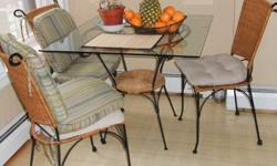 A very cute set of a table and three chairs. The table platform is composed of a thick sheet of glass. The table base is ornate wraught metal and wicker base shelve. Easily transportable. The three chairs are a matching set to the table base which are